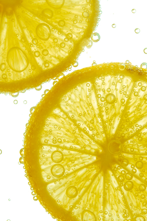 dazzling: Fresh lemon slice in water with bubbles on white background