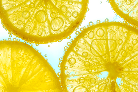 lemon slice: Fresh lemon slice in water with bubbles on sky background