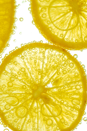 lemon slice: Fresh lemon slice in water with bubbles on white background