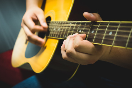 Close up hands playing acoustic guitar