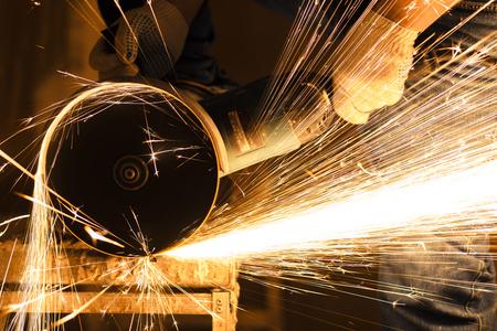 Worker cutting metal with big grinder. Lots of glowing sparks Standard-Bild