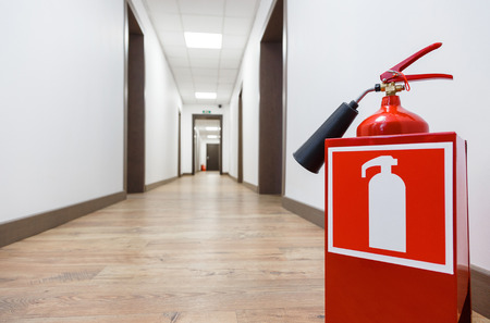 Fire extinguisher in empty business center corridor Stock Photo