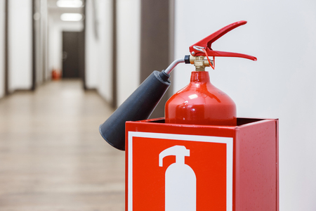 Fire extinguisher in white corridor of business center
