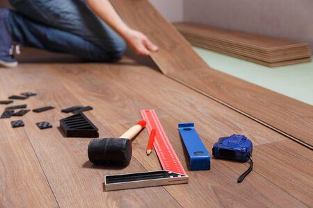 Mann, der Laminatboden legt. Auf dem Boden liegen verschiedene Zimmermannswerkzeuge Standard-Bild
