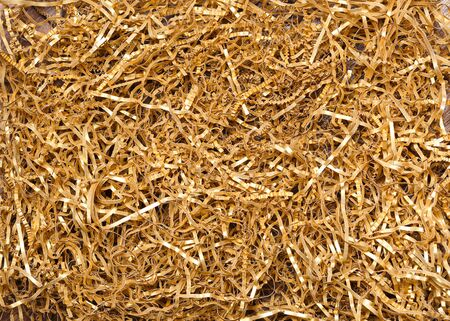 Golden shredded paper for gifting, shipping and stuffing. Top view.