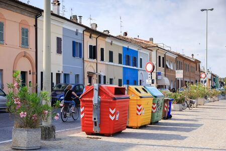 Large colorful garbage bins, trash cans, dedicated for separate collection of rubbish. Colorful buildings in center of Pesaro, Marche, Italy