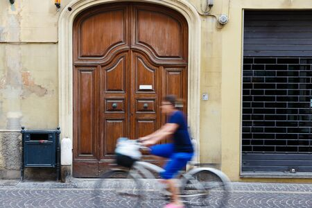 Typical Italian bicycler rides in ancient village in Tuscany, Italy. Motion blur