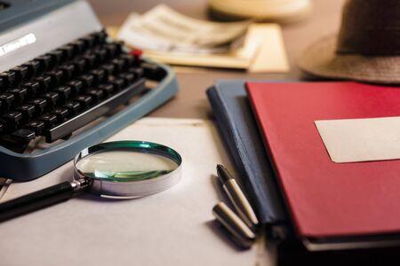 Escritorio de investigador con documentos confidenciales. Fondo de concepto de investigación de documentos secretos con lupa. Máquina de escribir vintage y sombrero viejo. Foto de archivo