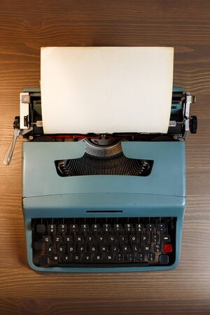 Vintage typewriter header with blank paper on wooden background, top view. Stockfoto