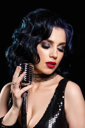 Beautiful sensual woman with retro microphone singing songs on the stage Standard-Bild