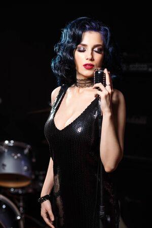 Beautiful sensual woman in black dress singing songs on the stage Standard-Bild