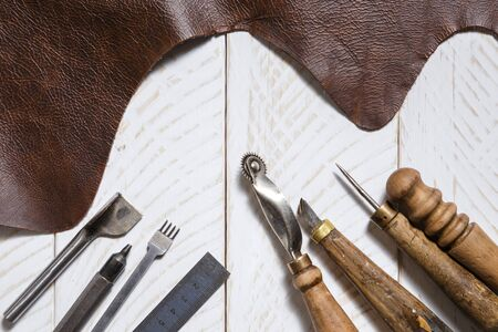 Crafting tools with cow leather on the white wooden boards. Top view
