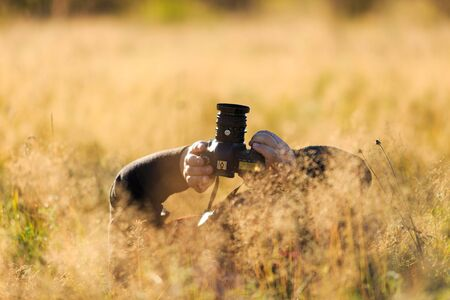 Nature photographer in the field with his DSLR camera Standard-Bild