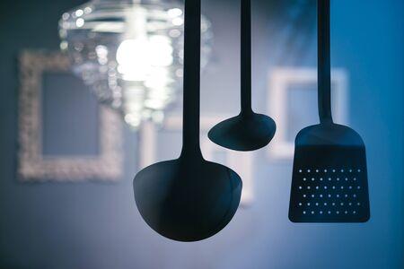 kitchen utensils hanging on a blue interior background. Standard-Bild
