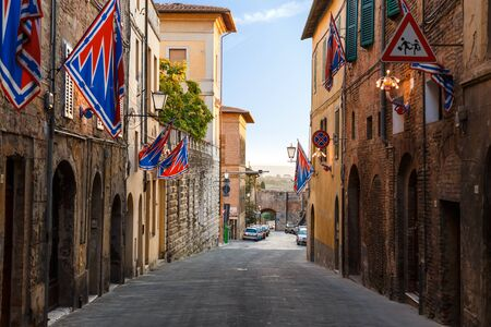Banners of the contrads on Medieval scenic street in Siena. Feast Palio. Region of Tuscany, Italy Standard-Bild