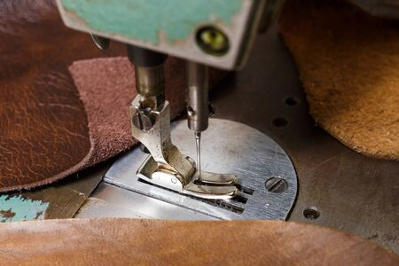 Old sewing machine and natural cow leathers. Selective focus