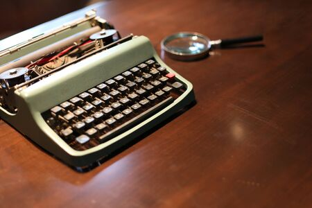 Retro typewriter and a magnifying glass on a wooden table 스톡 콘텐츠