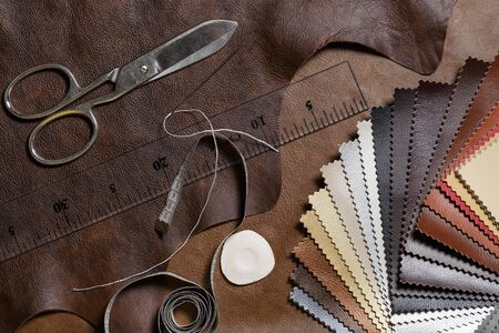 Crafting tools on natural cow leather in the tailoring workshop. Top view