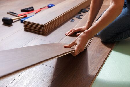 Male hands installing wooden laminate flooring. On the floor are different carpenter's tools