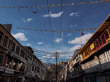 Tibetan prayer flags Om Mani Padme Hum hang between building at main bazaar in Leh Ladakh