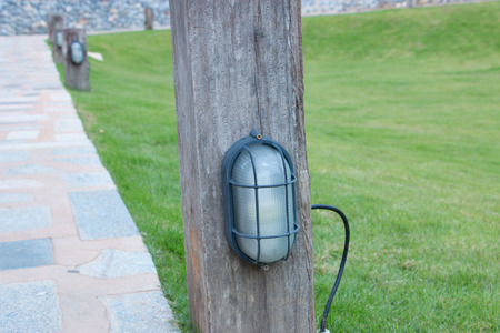 The Stone block walk path with garden lamp on green grass background photo
