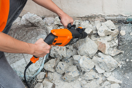 Man drills holes with drilling machine in stone block photo