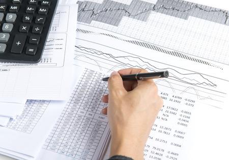 Handen van de accountant met calculator en pen. Accounting achtergrond.