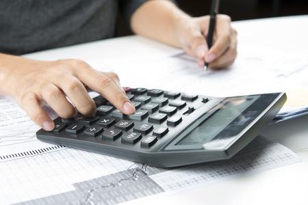 Handen van accountant met rekenmachine en pen. Boekhoudkundige achtergrond. Stockfoto