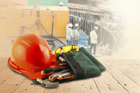 safety helmet and tools on wood table and building construction