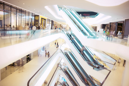 retail scene: People in motion in escalators at the modern shopping mall.