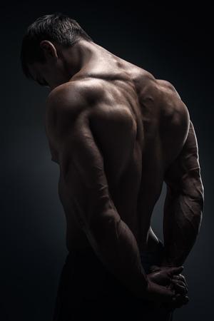Bodybuilder muscular considerável que levanta sobre o fundo preto