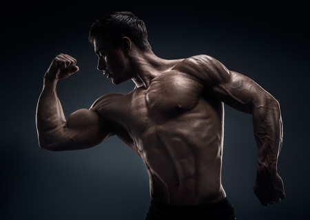 workout: Handsome muscular bodybuilder posing over black background Stock Photo