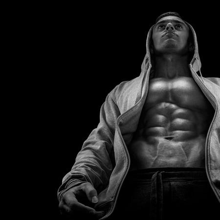 Onderste weergave van de jonge sterke bodybuilder pronken zijn lichaamsbouw tegen zwarte achtergrond. Vertrouwen jonge fitness man met sterke handen abs en buikspieren. Dramatisch licht.