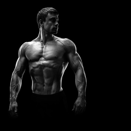Stunning muscular young men bodybuilder posing and looking behind. Studio shot on black background.
