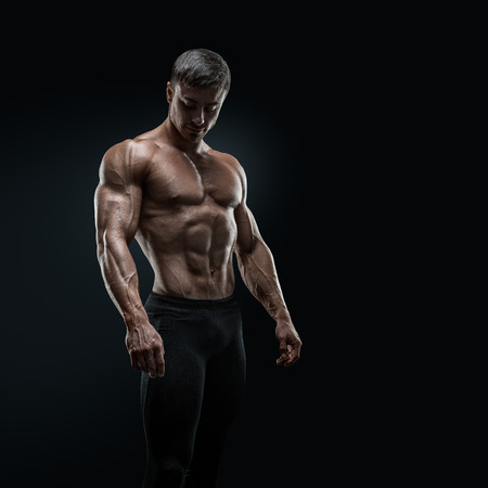 calisthenics: Muscular and fit young bodybuilder fitness male model posing over black background Stock Photo
