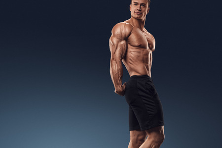 male torso: Muscular and fit bodybuilder fitness male model posing over black background. Strong and handsome young man demonstrate his muscular torso and biceps. Body of muscular male with great physique
