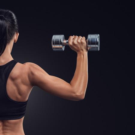 Fitness sportieve vrouw in opleiding het oppompen van de spieren van de rug en handen met halters