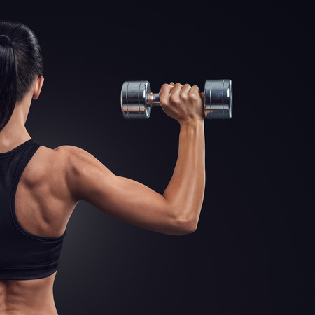 holding close: Fitness sporty woman in training pumping up muscles of the back and hands with dumbbells Stock Photo