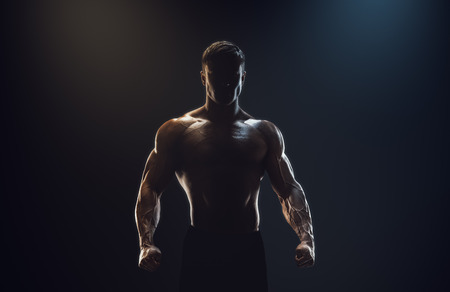фитнес: Силуэт сильный боец. Уверенный молодой человек фитнес с сильными руками и сжатыми кулаками. Драматический свет.