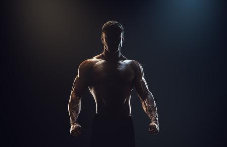 fitnes: Sylwetka silnego wojownika. Przekonany, młody człowiek z silnymi ćwiczeń rąk i zaciśniętymi pięściami. Dramatyczna światła. Zdjęcie Seryjne