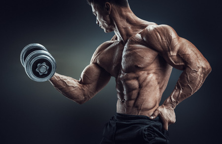 workout: Handsome power athletic man in training pumping up muscles with dumbbell. Strong bodybuilder with six pack perfect abs shoulders biceps triceps and chest. Image with clipping path