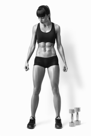 Fit female athlete in activewear ready to doing exercise with dumbbells. Strong abs showing. Black and white image with clipping path. Standard-Bild