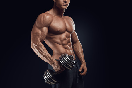 hands on stomach: Handsome power athletic man with dumbbell confidently looking forward. Strong bodybuilder with six pack perfect abs shoulders biceps triceps and chest