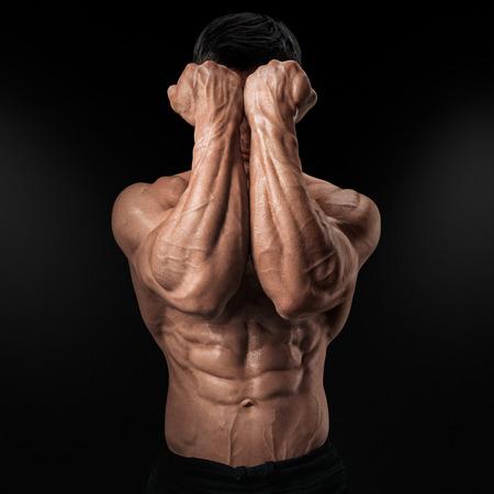 顔の前に 2 つの力の手。Abs. 強い man39s の腕筋と静脈のクローズ アップ、man39s の拳と。