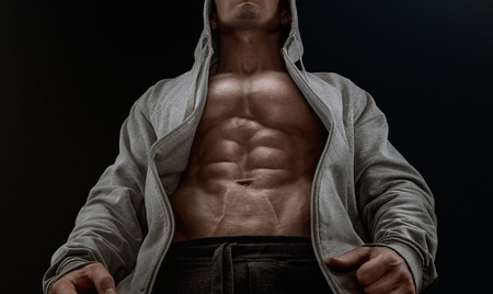 hoodie: Bottom view of young strong bodybuilder showing off his physique against black background. Confident young fitness man with strong hands abs and abdominal muscles. Dramatic light.