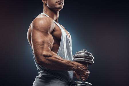 hombros: Hombre joven con mancuernas se preparan para flexionar los músculos sobre fondo oscuro. Atleta fuerte en ropa deportiva listo para hacer ejercicio con mancuernas con confianza mirando hacia adelante.