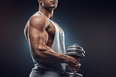 Young man with dumbbell prepare to flexing muscles over dark background. Strong athlete in activewear ready to doing exercise with dumbbell confidently looking forward.