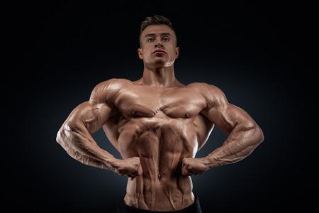culturista: Culturista muscular hermoso que presenta en el frente Lat ancho de la pantalla Spread lat desde el hombro espesor pecho delante Ancho brazo delantero y tama�o antebrazo masa cu�driceps y la separaci�n y el desarrollo de ternera desde el frente