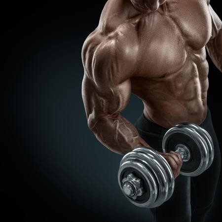 Primer plano de un poder guapo chico atlético culturista masculino haciendo ejercicios con mancuernas. Musculoso cuerpo fitness en el fondo oscuro.