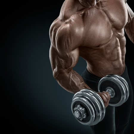 culturista: Primer plano de un poder guapo chico atlético culturista masculino haciendo ejercicios con mancuernas. Musculoso cuerpo fitness en el fondo oscuro. Foto de archivo